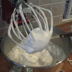 Whisk the egg whites (adding the sugar gradually) until stiff peaks are formed