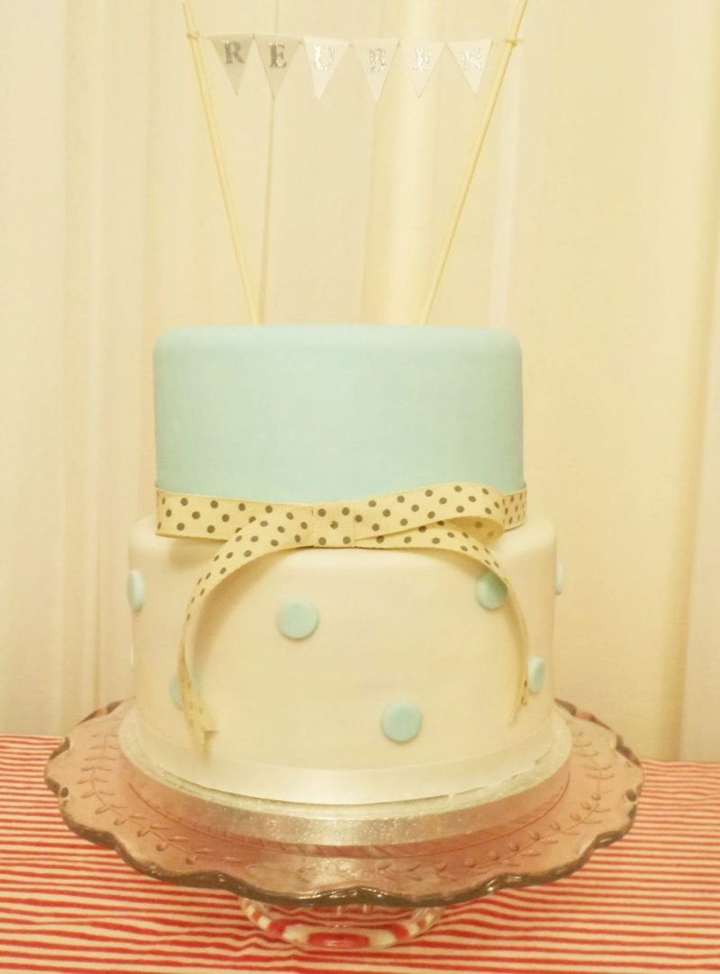 Christening cake. Two tiered iced fruit cake with duck egg blue polka dots and bunting